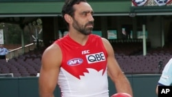 FILE - In this March 19, 2014 photo, Sydney Swans player Adam Goodes holds an Australian Rules Football at the Sydney Cricket Ground. Australians tend to laud their champions, so the fact that crowds continue to loudly boo him when he plays for the Sydney Swans in the nation-wide Australian Football League has both concerned and confounded Goodes to the point where he's considering retirement.