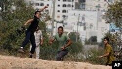 Muchachos israelíes lanzan piedras durante choques contra palestinos en las afueras del asentamiento judío de Kiryat Arba.