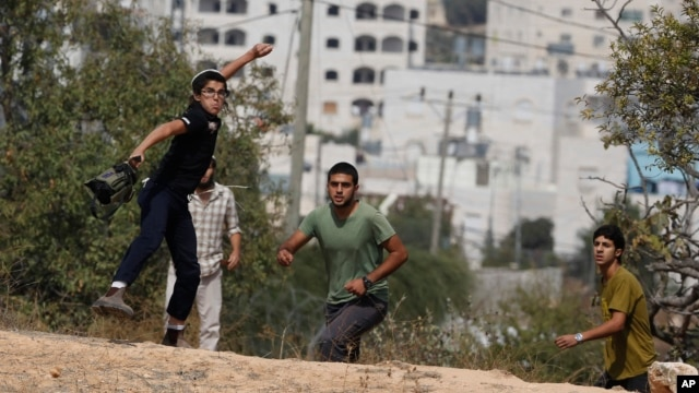 Israeli settler boys throw stones during clashes with Palestinians after a stabbing attack outside the Jewish settlement of Kiryat Arba in the West Bank, Friday, Oct. 9, 2015.