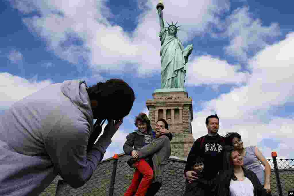 Tourists pose for photographs in front of the Statue of Liberty in New York Harbor in New York, Oct. 13, 2013. The Statue of Liberty reopened to the public after the state of New York agreed to shoulder the costs of running the site during the partial federal government shutdown.
