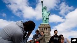 Para wisatawan yang mengunjungi New York hari Minggu (13/10), bisa kembali berkunjung ke komplek Patung Liberty yang kembali dibuka.