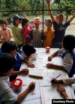 Stateless children in Thailand peer into the classroom of a school they are barred from attending. (Joseph Quinnell)