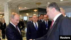 Presiden Rusia Vladimir Putin (kiri) berjabat tangan dengan Presiden Ukraina Petro Poroshenko dalam pertemuan di Minsk (26/8). (Reuters/Sergei Bondarenko)