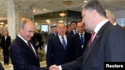 Presiden Rusia Vladimir Putin (kiri) berjabat tangan dengan Presiden Ukraina Petro Poroshenko di Minsk, Belarusia (26/8).