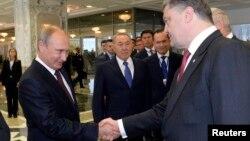 Russian President Vladimir Putin, left, shakes hands with his Ukrainian counterpart Petro Poroshenko, as Kazakh President Nursultan Nazarbayev watches, in Minsk, Aug. 26, 2014.
