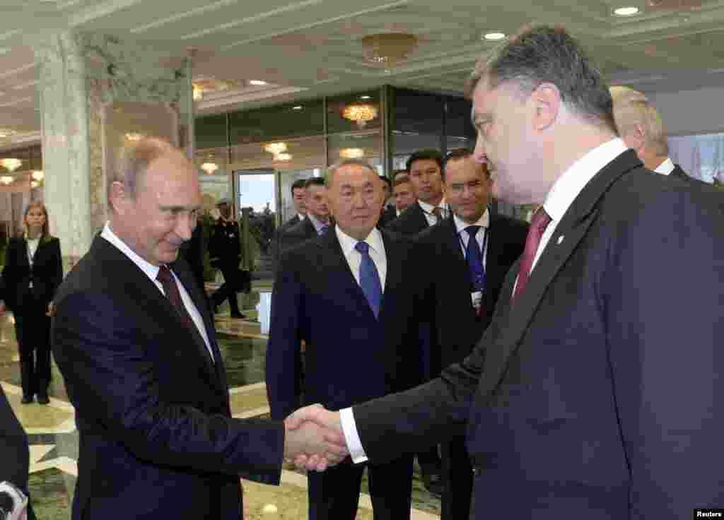 President Vladimir Putin (left) shakes hands with his Ukrainian counterpart Petro Poroshenko, as Kazakh President Nursultan Nazarbayev stands nearby, in Minsk, Aug. 26, 2014.