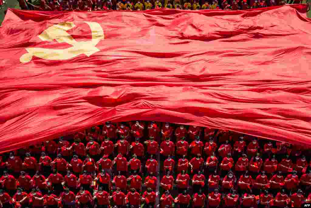 University students display a flag of the Communist Party of China to mark the party's 100th anniversary during an opening ceremony of the new semester in Wuhan in China's central Hubei province.