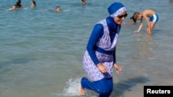 A woman wearing a burkini walks in the water August 27, 2016 on a beach in Marseille, France, the day after the country's highest administrative court suspended a ban on full-body burkini swimsuits that has outraged Muslims and opened divisions within the