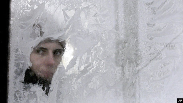 A woman looks through an icy window in a bus in Ukraine's capital, Kyiv, February 3, 2012.