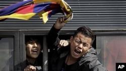 在中国驻印度大使馆外示威的西藏流亡者被抓进警车后仍然呼喊口号