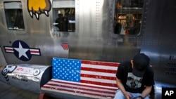 一位男士坐在北京某家出售美國名牌服裝的時尚精品店外繪有美國國旗圖案的長椅上看手機。(2019年5月13日)
