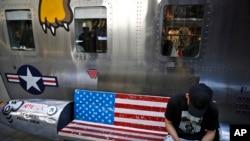 一位男士坐在北京某家出售美国名牌服装的时尚精品店外绘有美国国旗图案的长椅上看手机。(2019年5月13日)