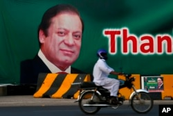A motorcyclist drives past a billboard showing the portrait of Pakistani Prime Minister Nawaz Sharif at a main highway in Islamabad, Pakistan, July 10, 2017.
