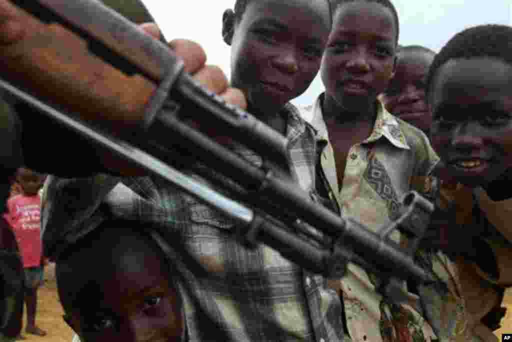 Des enfants s'approchent d'un homme armé en RDC. Au Congo, des dizaines d'enfants abandonnés dans la rue, sont exposés aux armes et sont parmi les premières vicitimes des bavures policières dénoncées. (AP Photo/John Bombengo).