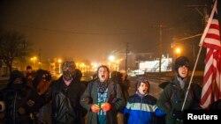 弗格森示威者在大陪审团裁定免予起诉密苏里州白人警察威尔逊后连续第三夜示威抗议,喊口号(2014年11月26日)