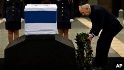 El presidente israelí, Simón Peres, deposita una ofrenda floral junto al féretro en la explanada del parlamento.