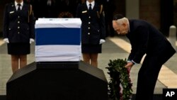 Presiden Israel Shimon Peres meletakkan karangan bunga di atas peti jenazah Sharon yang diletakkan di Knesset Plaza, gedung parlemen Israel di Yerusalem, Minggu (12/1).