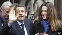 法国总统萨科齐和夫人4月22日在总统选举中投票后离开巴黎的一个投票站