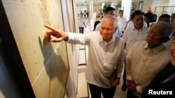 FILE - Philippines' Foreign Secretary Albert Del Rosario, points to a ancient map on display while Defense Secretary Voltaire Gazmin (R) looks on during the opening, at a Catholic university in Manila, Sept. 11, 2014.
