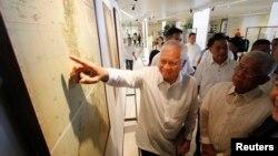 Ngoại trưởng Philippines Albert Del Rosario chỉ vào một bản đồ cổ bên cạnh Bộ trưởng Quốc phòng Voltaire Gazmin tại một trường đại học Công giáo ở Manila.