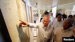 Ngoại trưởng Albert del Rosario của Philippines chỉ vào một bản đồ cổ được trưng bày tại một Đại học Công giáo ở Manila, 11/9/14