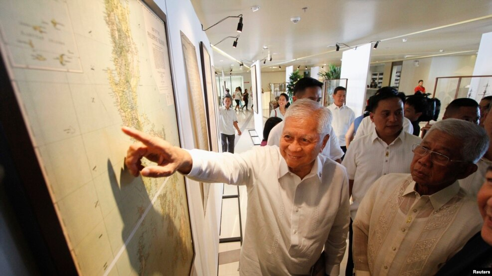 Ngoại trưởng Philippines Albert Del Rosario chỉ vào một bản đồ cổ trên màn hình bên cạnh Bộ trưởng Quốc phòng Voltaire Gazmin tại trường đại học Công giáo ở Manila (ảnh tư liệu năm 2014). Chính quyền của Tổng thống Philippines sắp rời nhiệm sở Benigno Aquino đã quyết định đưa Trung Quốc ra tòa đầu năm 2013.
