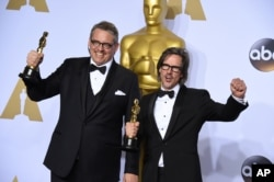 "Adam McKay, left, and Charles Randolph pose with the award for best adapted screenplay for ""The Big Short"" at the 2016 Oscars. (Photo by Jordan Strauss/Invision/AP)"