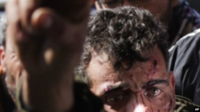 A wounded fighter is brought into a the Ras Lanuf Hospital from the battle in Bin Jawad on March 6, 2011.