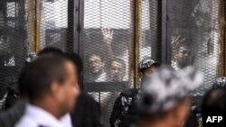 Des membres égyptiens des Frères musulmans interdits sont vus dans un quai de verre lors de leur procès à la capitale du Caire le 28 juillet 2018.