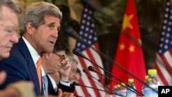 U.S. Secretary of State John Kerry, second left, speaks during a joint session on Climate Change issues with Chinese officials at the Diaoyutai State Guesthouse in Beijing, China, July 9, 2014.