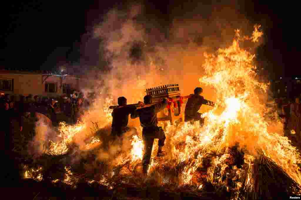 مردان چینی به مناسبت سال نو به همراه یک زیارتگاه سیار، از روی آتش می پرند.