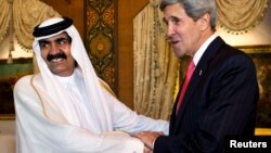 U.S. Secretary of State John Kerry (R) is greeted by Qatari Emir Hamad bin Khalifa Al Thani at Wajbah Palace in Doha, June 23, 2013.