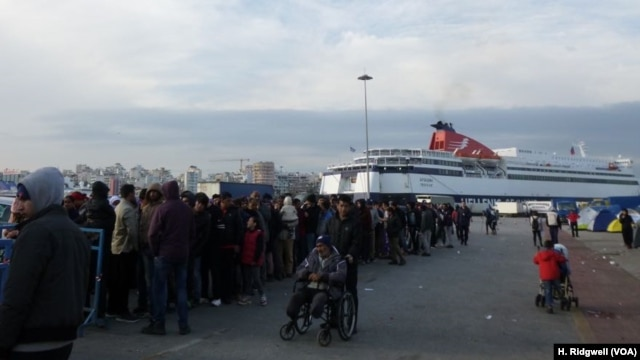 Refugees line up for food at Piraeus port, Athens, Greece, March 17, 2016.