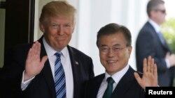 도널드 트럼프 미국 대통령(왼쪽)이 30일 워싱턴 백악관에서 문재인 한국 대통령을 영접한 후 취재진을 향해 함께 손을 흔들고 있다.