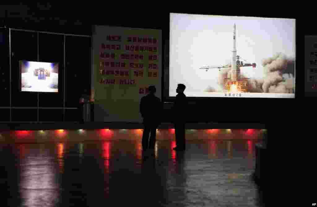 Oficiales de Corea del Norte permanecer cerca de una foto que representa el lanzamiento del satélite de cohetes en 2009 en la sala de exposiciones Tres Revoluciones de Pyongyang.