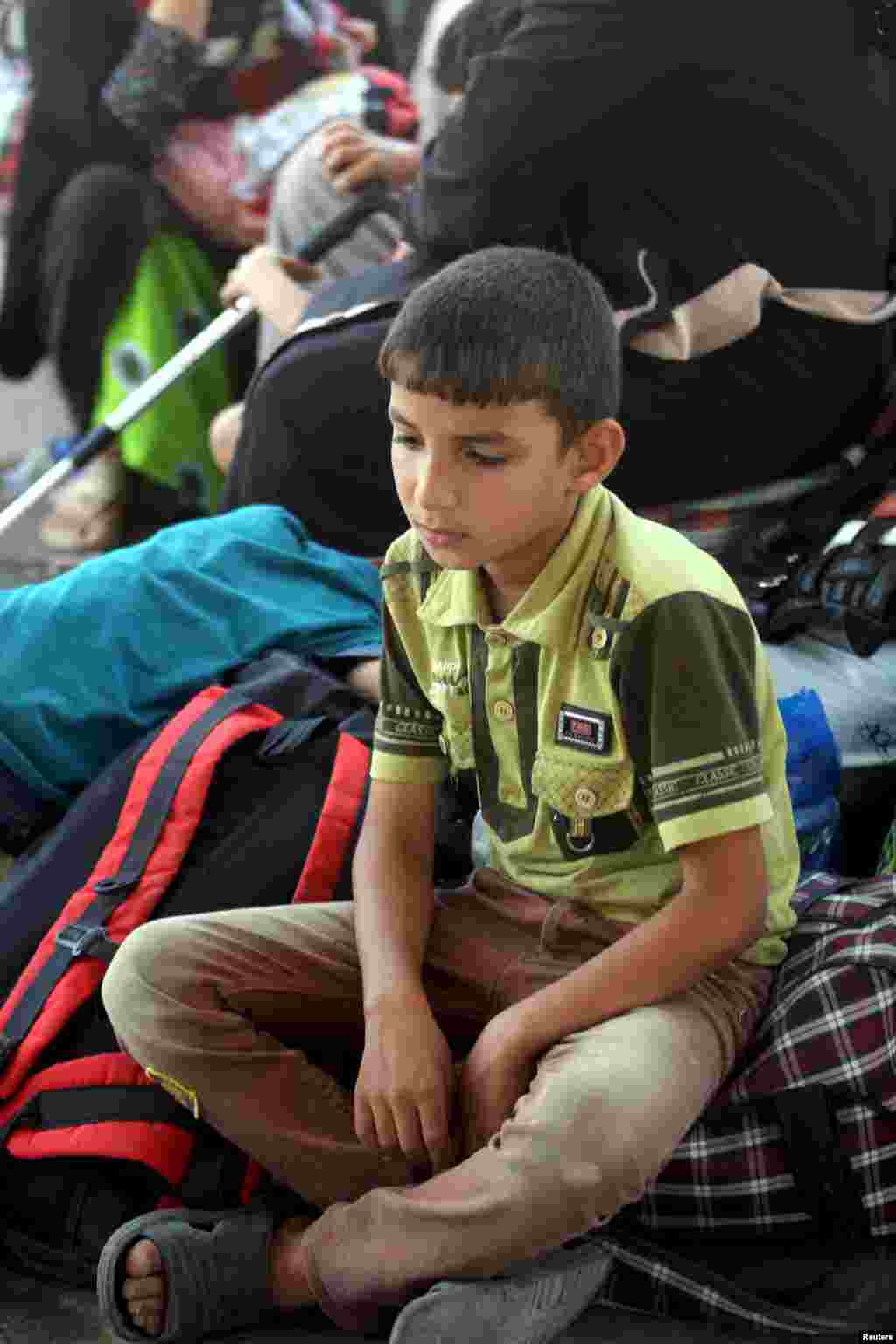 An internally displaced Iraqi Sunni boy sits with his family, who fled the violence in the city of Ramadi, on the outskirts of Baghdad, May 19, 2015.