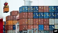 FILE- A container is loaded onto a cargo ship at the Tianjin port in China.
