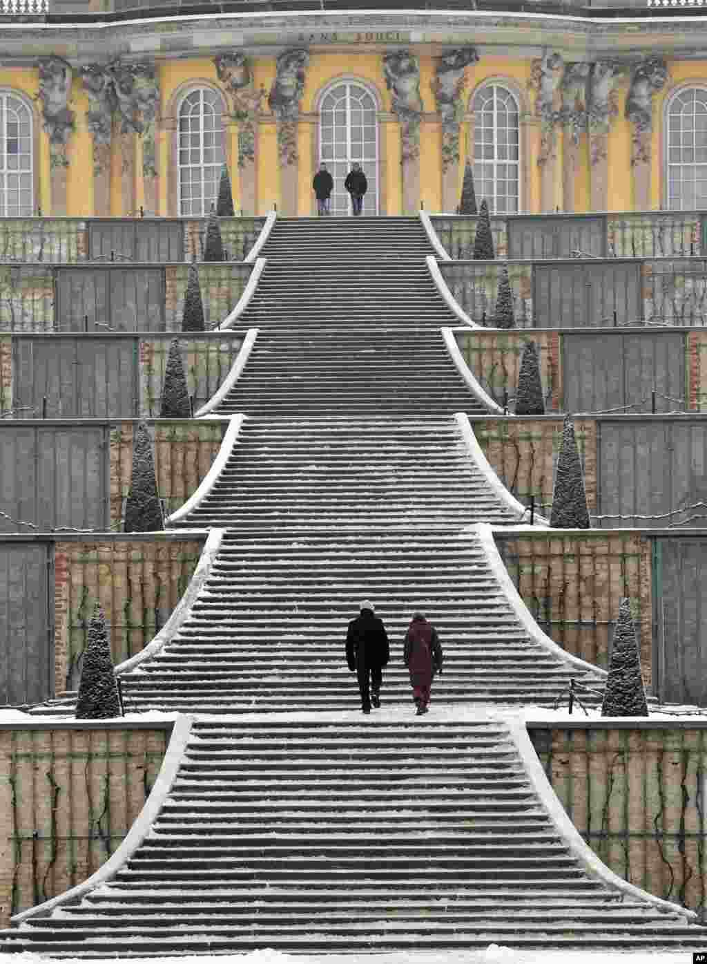 អ្នកទេសចរណ៍ដើរនៅលើជណ្តើរដែលមានព្រិលនៅព្រះរាជវាំង Sanssouci Palace ក្នុងក្រុង Potsdam ប្រទេសអាល្លឺម៉ង់។
