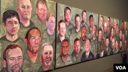 "A panoramic view of paintings from former president George W. Bush's ""Portraits of Courage"" series is seen at the Bush Presidential Museum in Dallas, Texas (K. Farabaugh/VOA). Afghanistan war veteran Johnnie Yellock's portrait is in the lower center of the first panel."