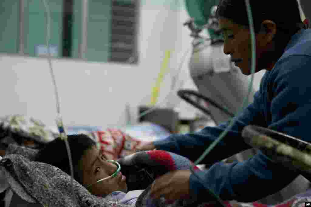 Aurelia Lopez, right, comforts her 12-year-old son Alex Fuentes, in the emergency room of a public hospital in San Marcos, Guatemala, November 7, 2012.