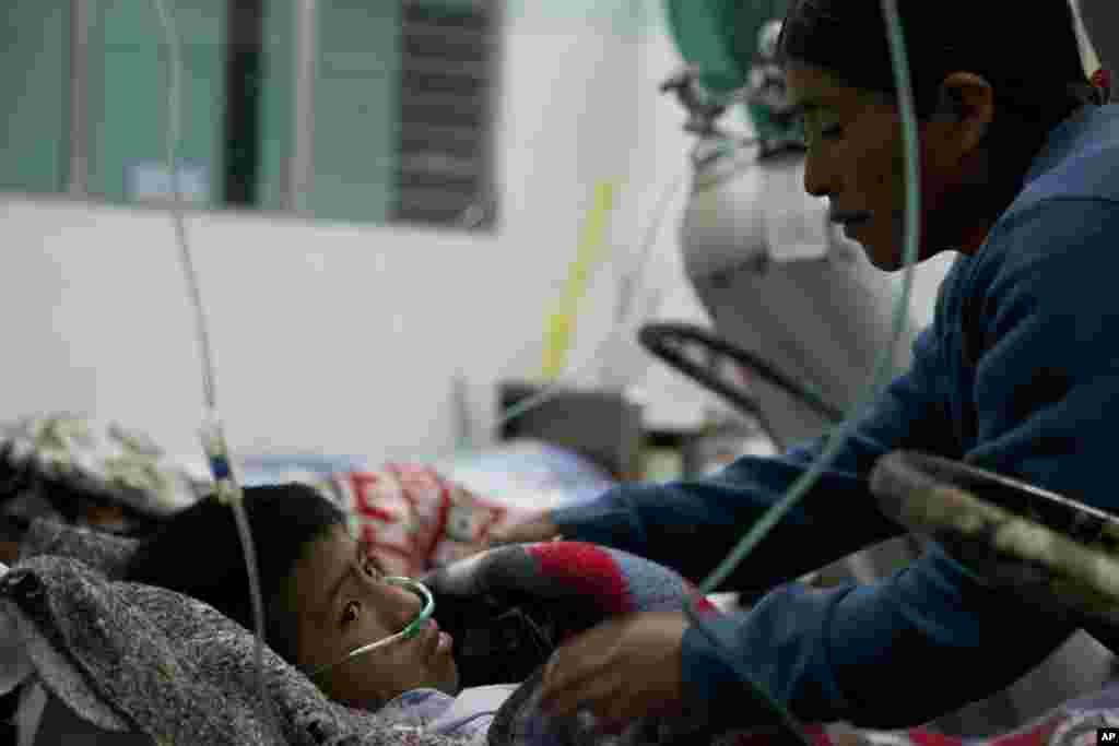 7일 산 마르코스 병원에서 지진 사태로 부상당한 아들을 간호하는 여성.