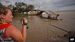 Seorang wanita merekam gambar dengan kamera video di wilayah Gelendzhik, selatan Rusia, yang tergenang banjir, Sabtu (7/7).