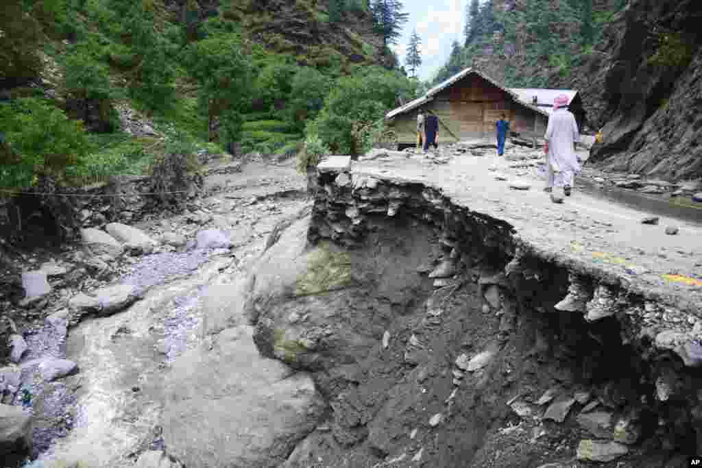 Villagers walk along a road washed away by heavy flooding in Neelum Valley of Pakistani controlled Kashmir.