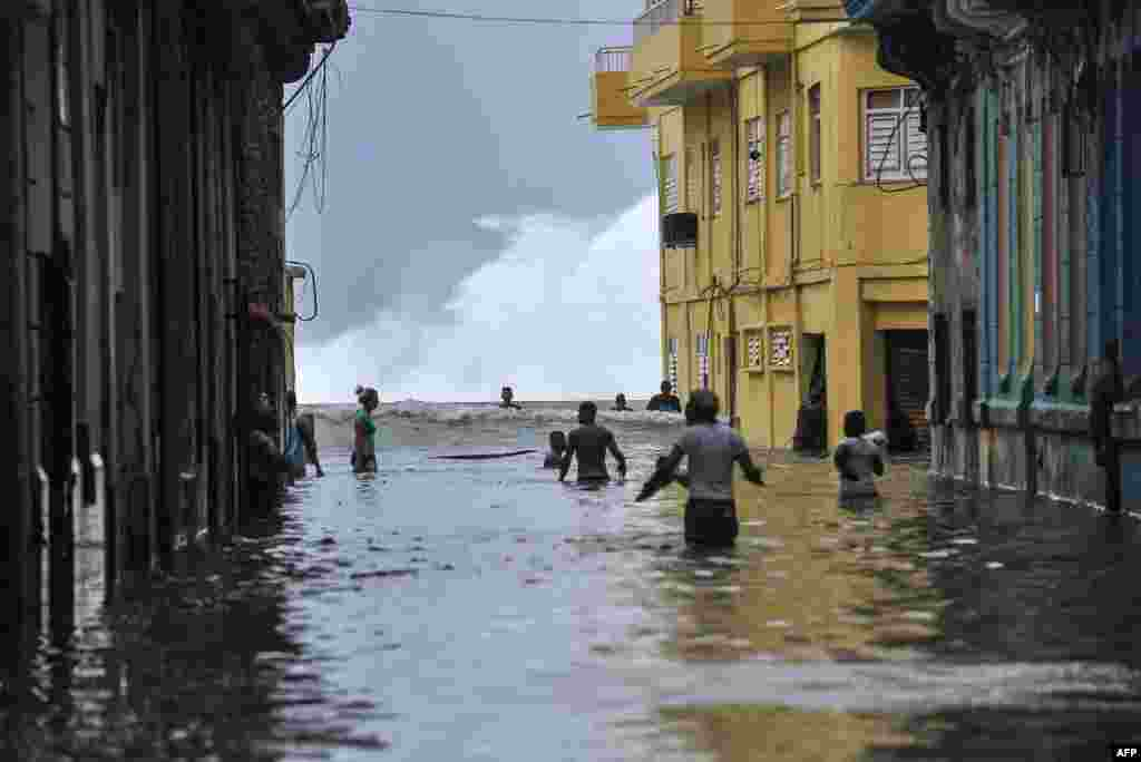 Cubans wade through a flooded street near the Malecon in Havana. Deadly Hurricane Irma battered central Cuba, knocking down power lines, uprooting trees and ripping the roofs off homes as it headed towards Florida.