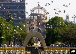 Doves fly during a ceremony at Hiroshima Peace Memorial Park in Hiroshima, Japan, Aug. 6, 2006.