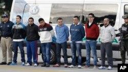 """Polisi mengawal ketat tujuh orang yang didakwa terlibat dalam kasus pembunuhan agen DEA James """"Terry"""" Watson di Bogota, Kolombia, sebelum diekstradiksi ke AS, 1 Juli 2014 (Foto: dok)."""