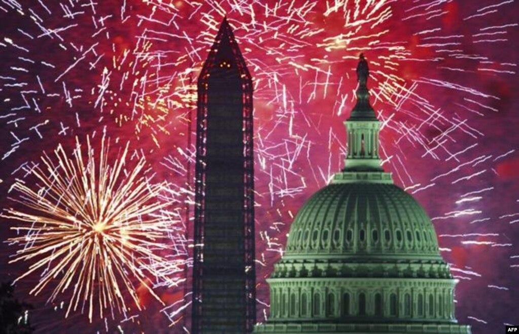 美国国庆节,首都华盛顿,礼花照亮夜空,辉映着国会大厦和华盛顿纪念碑(2013年7月4日)