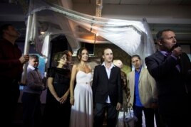 Bride Veronica (4th L) and her groom Michael (4th R), stand underneath a traditional Jewish wedding canopy during their secular wedding ceremony in Tel Aviv, Nov. 14, 2013