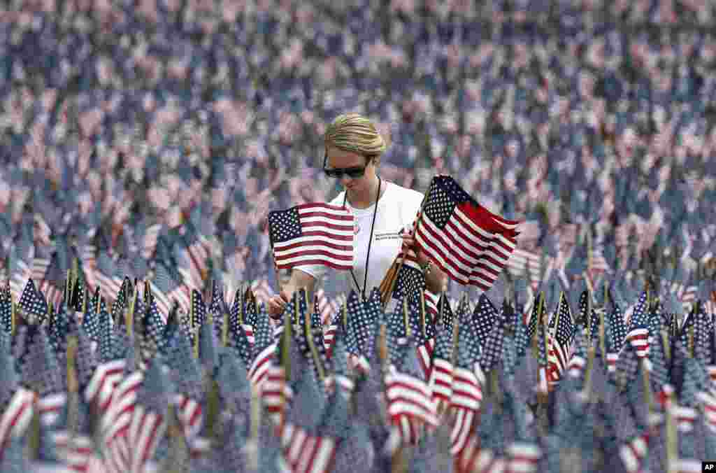 Shannon Day of Boston, a volunteer with Massachusetts Military Heroes Fund, replaces flags in the fund's flag garden on Boston Common in Boston, ahead of Memorial Day. Each of the approximately 37,000 flags represents a Massachusetts military member who died in service from the Revolutionary War to the present.