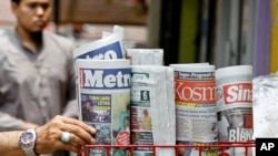 A man takes a copy of newspaper at a grocery shop in Shah Alam, Malaysia, Monday, March 26, 2018. Malaysia's government on Monday proposed new legislation to outlaw fake news with a 10-year jail term for offenders. (AP Photo/Sadiq Asyraf)